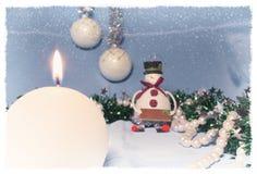 La natura morta di Natale con la candela bruciante ed il pupazzo di neve giocano Immagini Stock