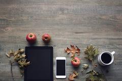 La natura morta di stagione di autunno con le mele, i dispositivi mobili, la tazza di caffè nero e la caduta rossi rimane il fond Fotografie Stock
