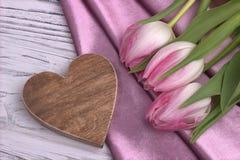 La natura morta elegante del giorno del ` s del biglietto di S. Valentino con il tessuto rosa dei fiori del tulipano ed il cuore  Fotografie Stock Libere da Diritti