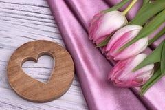 La natura morta elegante del giorno del ` s del biglietto di S. Valentino con il tessuto rosa dei fiori del tulipano ed il cuore  Fotografia Stock Libera da Diritti
