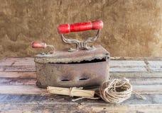 La natura morta retro con vecchio ferro arrugginito, il rotolo della carta e la corda annaspano Fotografia Stock