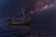 La nave arruinada bajo noche estrellada con claramente la vía láctea foto de archivo