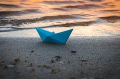 La nave azul de papel se lanza en la orilla arenosa del lago en la puesta del sol Fotos de archivo libres de regalías