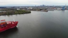 La nave cargada grande roja del contenedor del cargo llega el puerto industrial urbano en tiro aéreo asombroso del paisaje marino metrajes