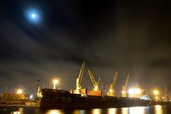 La nave da carico di caricamento con le gru è attraccata in porto alla notte Immagine Stock