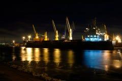 La nave da carico di caricamento con le gru è attraccata in porto alla notte Fotografia Stock