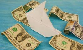 La nave de papel navega en ondas del dinero/de los dólares Foto de archivo