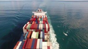 La nave del contenedor para mercancías navega a través del mar, olas oceánicas en el agua abierta 4k almacen de metraje de vídeo