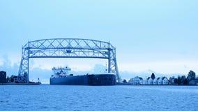 La nave del mineral de hierro llega debajo del puente de elevación aéreo de Duluth Minnesota del lago Superior almacen de metraje de vídeo
