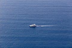 La nave navega en el agua azul hermosa cerca de la isla de Santorini, Imagen de archivo