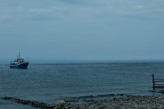 La nave nuota alla riva fotografia stock