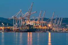 La nave porta-container sta scaricanda nel porto marittimo internazionale di Capodistria a tarda sera fotografie stock libere da diritti