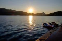 La nave que flota en un río o un lago al lado del embarcadero con vistas a las montañas Foto de archivo