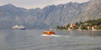 La navette de passager livre des passagers à un grand revêtement de croisière ancré dans la baie de Boka Kotorska photos libres de droits