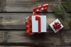 La Navidad, Año Nuevo blanco, caja de regalo, cinta roja, fondo de madera, visión superior, vintage, espacio para el texto Entreg fotografía de archivo