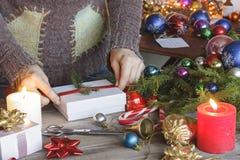 La Navidad, Año Nuevo La mujer, regalos llenos, envueltos de la Navidad, encendidos vela, las decoraciones de la Navidad, hace fr Imágenes de archivo libres de regalías