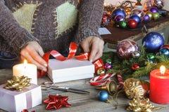 La Navidad, Año Nuevo La mujer, regalos llenos, envueltos de la Navidad, encendidos vela, las decoraciones de la Navidad, hace fr Fotos de archivo libres de regalías