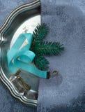 La Navidad, Año Nuevo platos de plata, cinta azul del satén y ramitas spruce Visión superior Fotografía de archivo