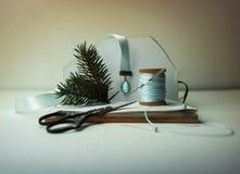La Navidad, Año Nuevo Preparación para el día de fiesta - cuaderno, tijeras, hilo, cinta de seda, rama del abeto Fotografía de archivo