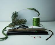 La Navidad, Año Nuevo Preparación para el día de fiesta - cuaderno, tijeras, hilo, cinta de seda, rama del abeto Fotografía de archivo libre de regalías