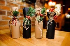 La Navidad adorable cuatro adornó las botellas con las cintas y la rama del abeto fotografía de archivo