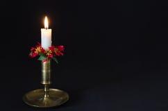 La Navidad adornó la vela en un fondo negro Imagenes de archivo