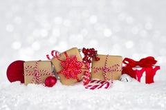 La Navidad adornó las cajas de regalo en nieve sobre fondo abstracto Imagenes de archivo