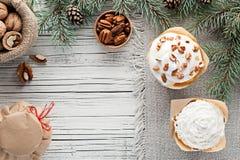 La Navidad adornó las magdalenas en la opinión superior del fondo de madera blanco Foto de archivo libre de regalías