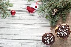 La Navidad adornó las magdalenas en la opinión superior del fondo de madera blanco Foto de archivo