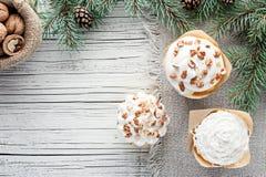 La Navidad adornó las magdalenas en la opinión superior del fondo de madera blanco Imágenes de archivo libres de regalías