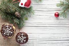 La Navidad adornó las magdalenas en la opinión superior del fondo de madera blanco Imagen de archivo libre de regalías