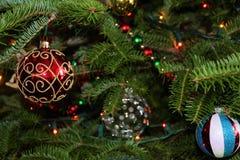 La Navidad adorna brillar intensamente en un árbol de pino verde Fotos de archivo libres de regalías