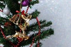 La Navidad adorna la ejecución en el árbol de navidad sobre el giltter blanco Fotos de archivo