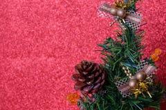 La Navidad adorna la ejecución en el árbol de navidad sobre el giltter rojo b Fotos de archivo