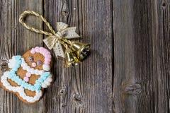 La Navidad Bell y galleta del pan de jengibre en la placa de madera Imagen de archivo libre de regalías