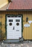 La Navidad blanca adornó la puerta en la casa vieja Foto de archivo libre de regalías