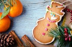 La Navidad, composición del Año Nuevo con el hombre de pan de jengibre, mandarinas, conos del árbol de abeto, del pino y canela D Imagen de archivo