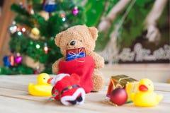 La Navidad con adornan y las cajas de regalo del oso de peluche en el tablero de madera Fotografía de archivo