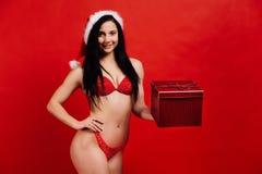 La Navidad, días de fiesta del ` s del Año Nuevo Muchacha hermosa de los deportes atractivos en el bikini Papá Noel con la caja d Imagen de archivo