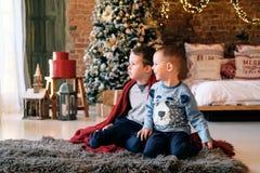 La Navidad, días de fiesta y concepto de la niñez - hermanos felices que se sientan en el piso, soñando, para Papá Noel que esper imagen de archivo