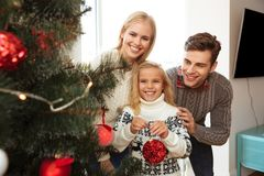 La Navidad de adornamiento feliz tr del padre, de la madre y de la pequeña hija Fotos de archivo libres de regalías
