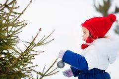 La Navidad de adornamiento tres de la niña al aire libre Imágenes de archivo libres de regalías