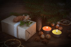 La Navidad de Eco empaqueta el regalo y dos velas ligeras Fotos de archivo libres de regalías