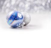 La Navidad de plata y azul adorna bolas en fondo del bokeh del brillo con el espacio para el texto Navidad y Feliz Año Nuevo Imagen de archivo