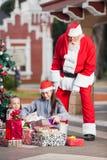 La Navidad de Santa Claus Looking At Children Opening Fotografía de archivo