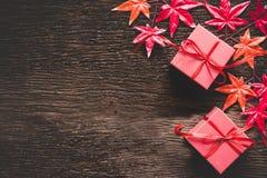 La Navidad decorativa en fondo de madera con la decoración roja, arce, y una muestra o una tarjeta vacía para los saludos, Foto de archivo libre de regalías