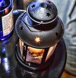 La Navidad del Año Nuevo Champán en vidrios y en una botella, una linterna de la Navidad con una vela ardiente en la tabla festiv Imagen de archivo