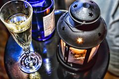 La Navidad del Año Nuevo Champán en vidrios y en una botella, una linterna de la Navidad con una vela ardiente en la tabla festiv Foto de archivo libre de regalías