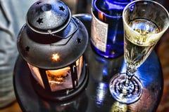 La Navidad del Año Nuevo Champán en vidrios y en una botella, una linterna de la Navidad con una vela ardiente en la tabla festiv Imagen de archivo libre de regalías