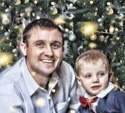 La Navidad del Año Nuevo La familia joven feliz con un pequeño hijo que sonríe feliz resuelve el Año Nuevo en casa Árbol de navid Fotografía de archivo libre de regalías